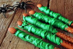 Halloween witches finger candy dipped pretzel rods, on wood Royalty Free Stock Photo