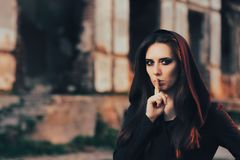 Halloween Woman Keeping a Secret in Front of a Ruins. Hooded woman with finger on the lips waiting for the night to come stock photo