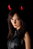 Halloween woman portrait in studio. Sexy brunette girl wearing a halloween costume of a devil. Beautiful mixed race Caucasian Asian young girl posing against Royalty Free Stock Images