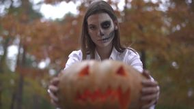 Halloween. Woman with a scary Halloween makeup holding a pumpkin in his hands. Girl with a scary Halloween makeup holding a pumpkin in his hands. Halloween stock video footage