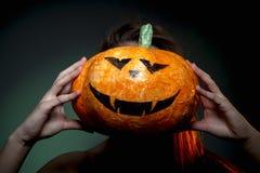 Halloween, woman in underwear with pumpkin in his hands. Portrait on dark green background. Halloween, woman in underwear with pumpkin in his hands. Portrait on stock photo