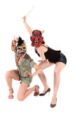 Halloween women masks. Young Halloween women with ugly scary masks, fighting. Studio shot. White background Royalty Free Stock Images