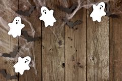 Halloween corner border of spiderwebs, and ghost & bats on wood Royalty Free Stock Image