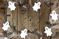 Halloween frame of spiderwebs, and ghost & bats on wood Royalty Free Stock Images