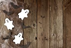 Halloween side border of spiderwebs, and ghost & bats on wood Stock Images