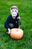 Halloween: young boy wearing skull mask. Young boy wearing skull mask attacking halloween pumpkin Stock Photos