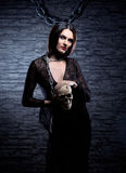 Halloween: young and sexy witch holding a skull Stock Images