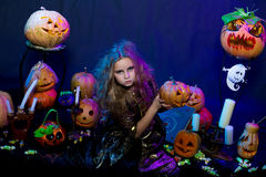 Halloween, young witch. Teenage girl dressed as a witch with a lot of pumpkins. Studio photo Royalty Free Stock Images