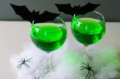 Halloween zieleni koktajl, Toksyczny napój Dekorujący z pająkami, pajęczyna i czerń nietoperze na Ciemnym tle, obrazy stock