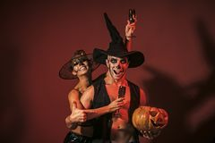 Halloween Zombie party and horror. Halloween Holiday and celebration. couple with makeup on brown background. Couple in love with pumpkin and wine glass. women royalty free stock photography