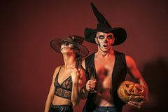 Halloween Zombie party and horror. Women and men has happy face in witch hat. couple with makeup on brown background. Halloween Holiday and celebration. Couple stock image