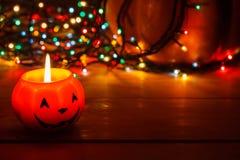 Halloweenowa świeczka w zmroku na drewnianym tle Za banią w światłach girlanda obrazy stock
