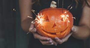 Halloweenowa bania w rękach dziewczyna z Bengalia światłami Wakacyjny Halloweenowy pojęcie Piękna kobieta z baniami zdjęcie stock