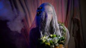 Halloweenowa czarownica z magiczną banią w zmroku Piękna młoda kobieta w czarownicach kapelusz i kostiumu mieniu rzeźbił bani zbiory wideo