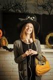 Halloweenowa dziewczyna w czarownica kapeluszu z hełmofonami i torby ono uśmiecha się obraz stock