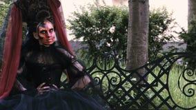 Halloweenowa dziewczyna w czarownicy obsiadaniu na ławce w miasto parka tajemnicie lasowym horroru pojęciu i zdjęcie wideo