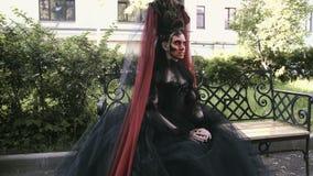 Halloweenowa dziewczyna w czarownicy obsiadaniu na ławce w miasto parka tajemnicie lasowym horroru pojęciu i zbiory wideo