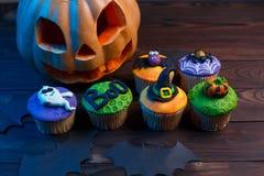 Halloweenowe babeczki z barwionymi dekoracjami: bania, duch, spi fotografia stock