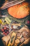 Halloweenowy śniadaniowy pojęcie Na stole kłama bani, cukierków i jabłek w karmelu, zdjęcia royalty free