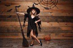 Halloweenowy czarownicy pojęcie - Długi strzał mały caucasian czarownicy dziecko pozuje z magicznym broomstick nad nietoperza i p Obraz Stock