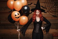 Halloweenowy czarownicy pojęcie - Piękna caucasian kobieta świętuje Halloween pozuje z pozować z pomarańcze i bla w czarownica ko Fotografia Stock