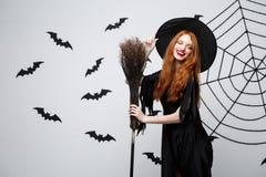 Halloweenowy czarownicy pojęcie - portret piękna młoda czarownica z broomstick nad popielatą ścianą z nietoperza i pająka siecią Obraz Stock