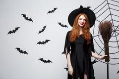 Halloweenowy czarownicy pojęcie - portret piękna młoda czarownica z broomstick nad popielatą ścianą z nietoperza i pająka siecią Zdjęcia Royalty Free