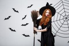 Halloweenowy czarownicy pojęcie - portret piękna młoda czarownica z broomstick nad popielatą ścianą z nietoperza i pająka siecią Zdjęcie Royalty Free