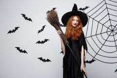 Halloweenowy czarownicy pojęcie - portret piękna młoda czarownica z broomstick nad popielatą ścianą z nietoperza i pająka siecią Obrazy Stock