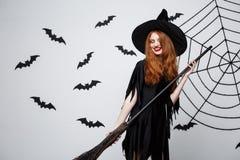 Halloweenowy czarownicy pojęcie - portret piękna młoda czarownica z broomstick nad popielatą ścianą z nietoperza i pająka siecią Obraz Royalty Free