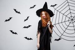 Halloweenowy czarownicy pojęcie - portret piękna młoda czarownica z broomstick nad popielatą ścianą z nietoperza i pająka siecią Zdjęcie Stock