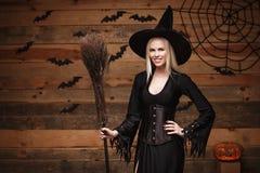 Halloweenowy czarownicy pojęcie - Szczęśliwy Halloweenowy Seksowny czarownicy mienie pozuje nad starym drewnianym pracownianym tł Obrazy Royalty Free
