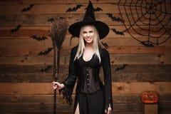 Halloweenowy czarownicy pojęcie - Szczęśliwy Halloweenowy Seksowny czarownicy mienie pozuje nad starym drewnianym pracownianym tł Obrazy Stock