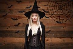 Halloweenowy czarownicy pojęcie - Szczęśliwy Halloweenowy Seksowny czarownicy mienie pozuje nad starym drewnianym pracownianym tł Zdjęcie Stock