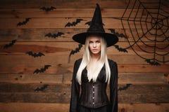 Halloweenowy czarownicy pojęcie - Szczęśliwy Halloweenowy Seksowny czarownicy mienie pozuje nad starym drewnianym pracownianym tł Fotografia Royalty Free