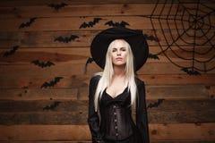 Halloweenowy czarownicy pojęcie - Szczęśliwy Halloweenowy Seksowny czarownicy mienie pozuje nad starym drewnianym pracownianym tł Zdjęcie Royalty Free