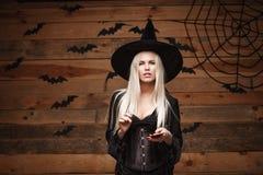 Halloweenowy czarownicy pojęcie - Szczęśliwy Halloweenowy Seksowny czarownicy mienie pozuje z smartphone nad starym drewnianym pr Zdjęcia Stock