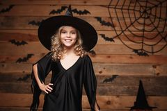 Halloweenowy czarownicy pojęcie - zbliżenia mały caucasian szczęśliwy czarownicy dziecko pozuje nad nietoperza i pająka sieci tłe Fotografia Stock