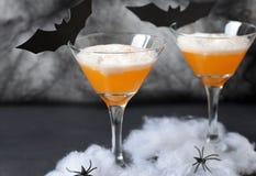 Halloweenowy Dyniowy koktajl, Toksyczny Pomarańczowy napój Dekorujący z pająkami, pajęczyna i czerń nietoperze na Ciemnym tle, fotografia stock