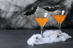 Halloweenowy Dyniowy koktajl, Toksyczny Pomarańczowy napój Dekorujący z pająkami, pajęczyna i czerń nietoperze na Ciemnym tle, obraz royalty free