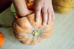 Halloweenowy dyniowy rozcięcie proces, męskie ręki bierze out ziarna i resztki od bani Obrazy Stock