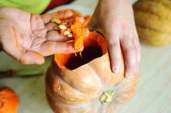 Halloweenowy dyniowy rozcięcie proces, męskie ręki bierze out ziarna i resztki od bani Obraz Royalty Free