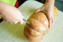 Halloweenowy dyniowy rozcięcie proces, samiec ręki z nożem, ziarna i resztki na kuchennym stole, zdjęcia royalty free