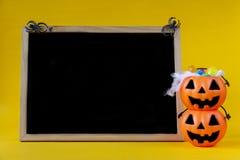 Halloweenowy Jack o Latarniowy wiadro i pustego miejsca chalkboard na żółtym b obrazy stock
