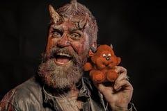 Halloweenowy modniś z satan rogami, krwiste rany trzyma miękkiego potwora zdjęcia royalty free