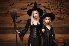 Halloweenowy pojęcie rozochocona matka i jej córka w czarownica kostiumach świętuje Halloween pozuje z wyginać się baniami nad ni Zdjęcia Stock