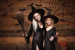 Halloweenowy pojęcie rozochocona matka i jej córka w czarownica kostiumach świętuje Halloween pozuje z wyginać się baniami nad ni Obrazy Royalty Free