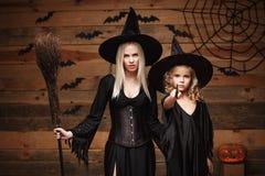Halloweenowy pojęcie rozochocona matka i jej córka w czarownica kostiumach świętuje Halloween pozuje z wyginać się baniami nad ni Zdjęcie Royalty Free
