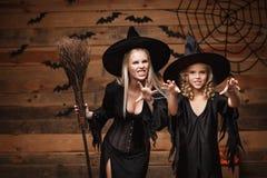 Halloweenowy pojęcie rozochocona matka i jej córka w czarownica kostiumach świętuje Halloween pozuje z wyginać się baniami nad ni Obrazy Stock
