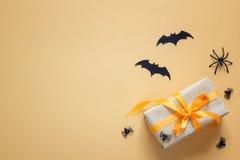 Halloweenowy tło z prezenta pudełkiem, dekoracyjnymi pająkami i nietoperzami, obraz royalty free